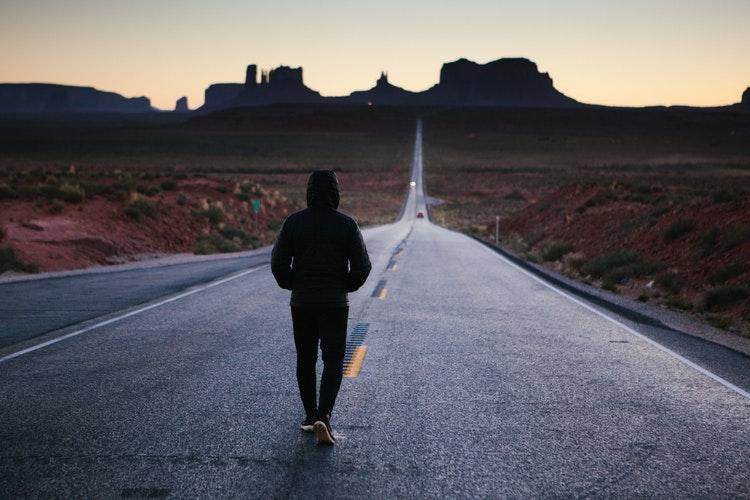 A MAN WALKING INTO SUNSET